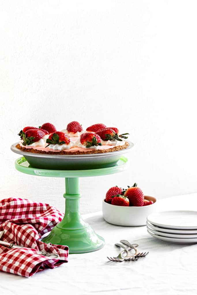 Strawberry Jello Pie with Cool Whip and graham cracker crust on a green dessert stand.