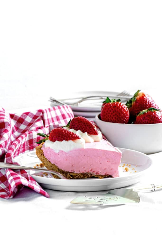 Slice of Jello Cool Whip pie. This no-bake dessert is garnished with whipped cream & strawberries.