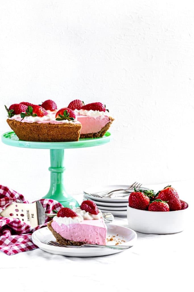 Strawberry Jello Cool Whip Pie (no-bake dessert) on green dessert stand.
