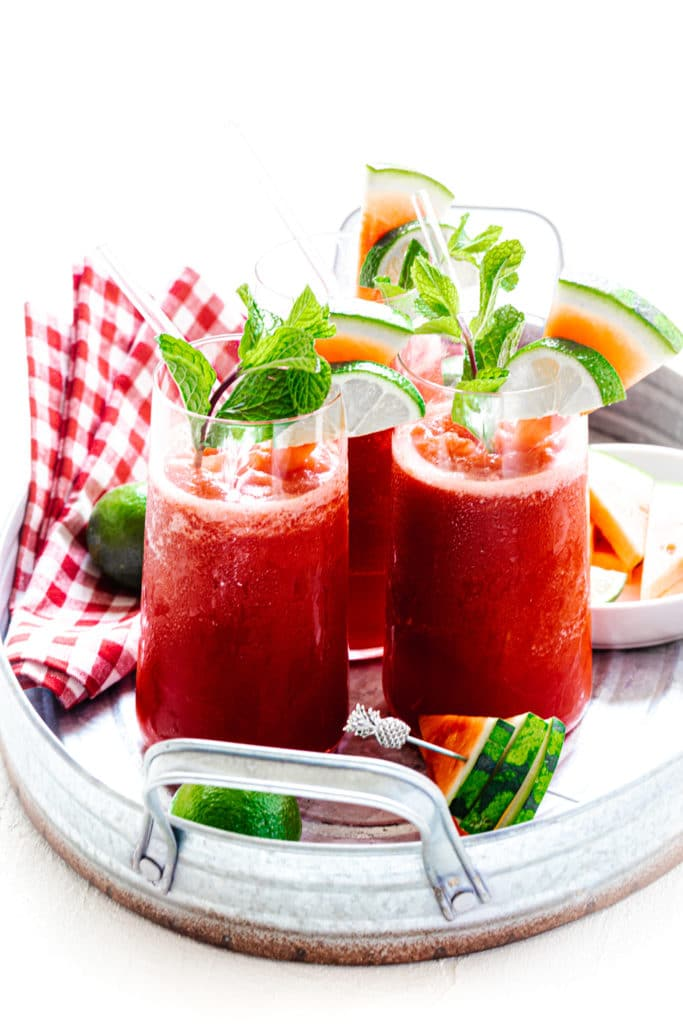 3 glasses watermelon slushie garnished with mint, lime slices, and watermelon slices on metal serving tray.