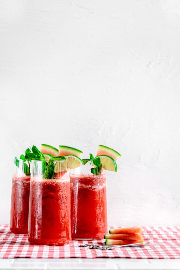 3 tall glasses of watermelon slushie with glass straws. Drinks are garnished with watermelon slices, mint and limes.