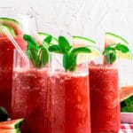 Frozen watermelon drink in glass pitcher with 3 tumblers of watermelon slushie with glass straws.
