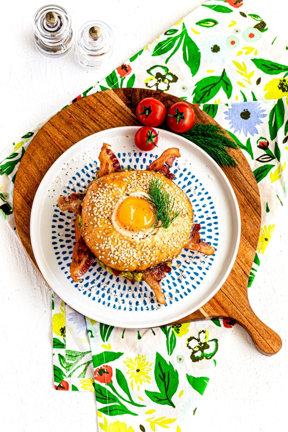 A bagel breakfast sandwich plated and served on a wooden board.