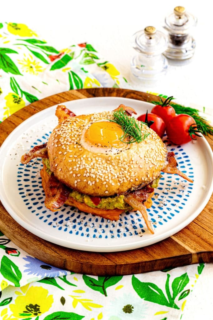 Bagel breakfast sandwich on a plate with a tomato and dill garnish, and salt and pepper.