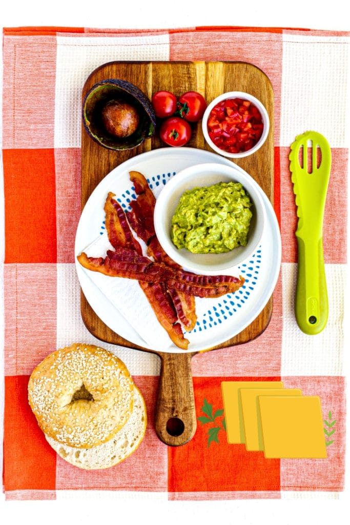 Recipe prep for Bagel Breakfast Sandwich: mashed avocado, diced tomatoes, fried bacon, sliced bagel.