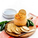 Jalapeno Pimento Cheese dip in a glass bowl with metal spreader on a wooden board.