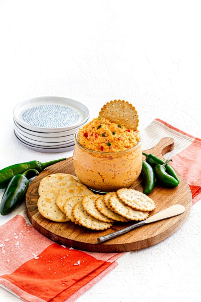 Southern Pimento Cheese dip in a glass bowl with metal spreader on a wooden board.