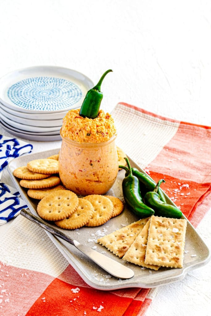 Homemade Jalapeno Pimento Cheese Dip served in a glass jar on a small appetizer platter with crackers.
