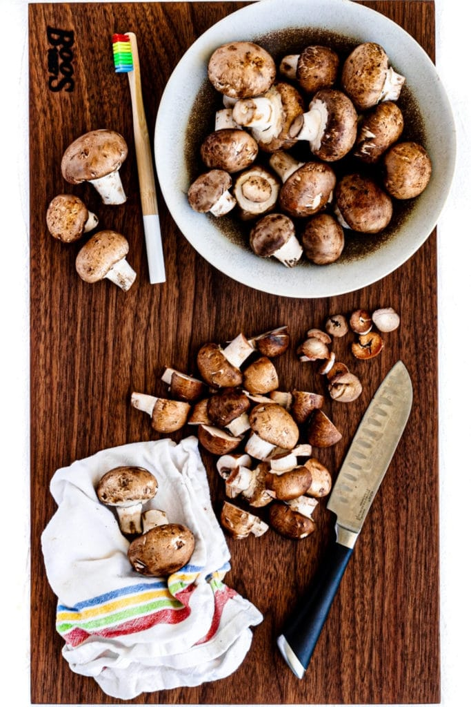 Mushrooms on a cutting board. Showing how to clean and slice mushrooms before sauteing.