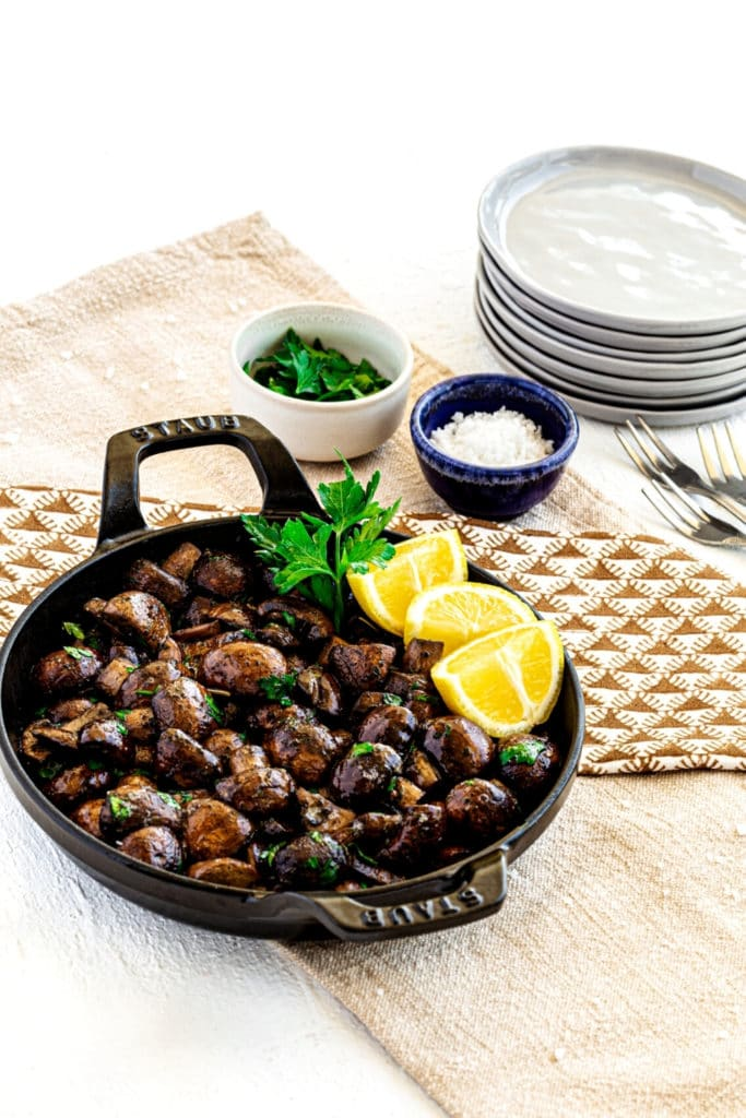 Sauteed mushrooms garnished with parsley and lemon wedges in a small round cast-iron server.