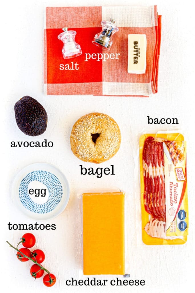 Ingredients for egg-in-a-hole Bagel Breakfast Sandwich: butter, bagel, egg, bacon, avocado, cheese, tomato.