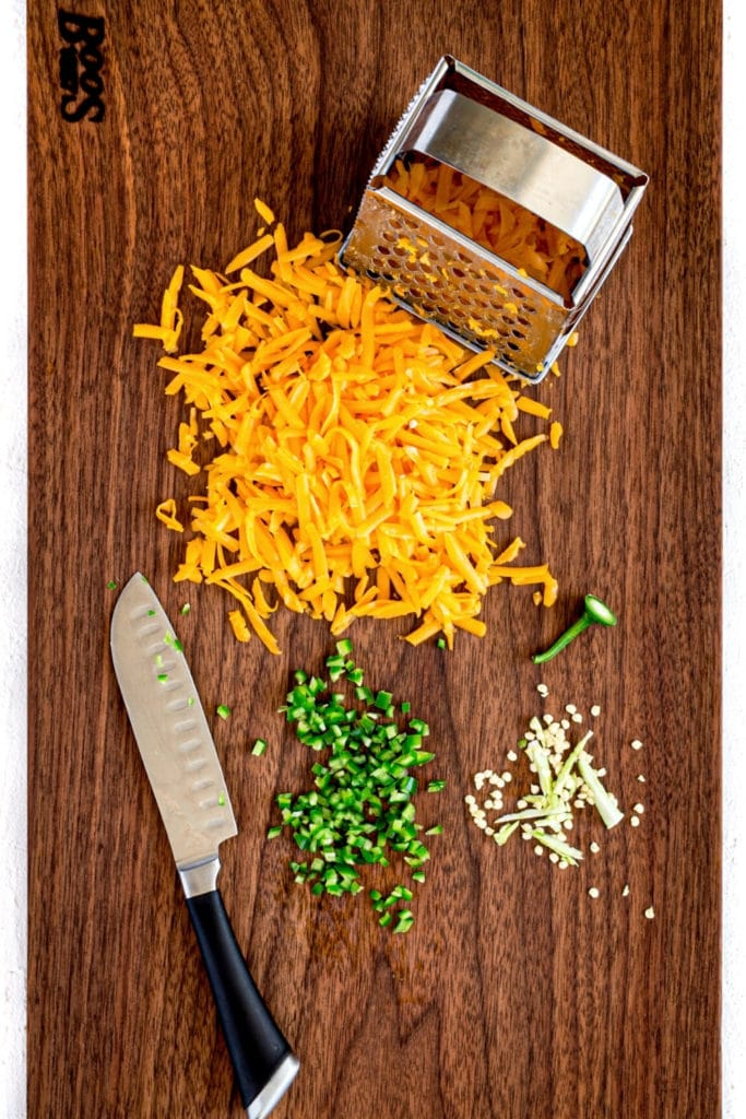 Cheddar cheese, metal grater, knife and jalapeno on wooden board for pimento cheese recipe.