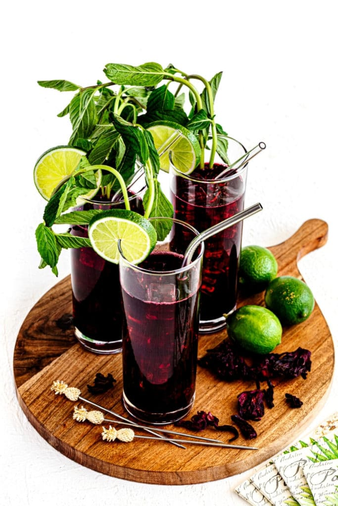 Rustic wooden serving tray with 3 glasses of Agua de Jamaica Hibiscus Sweet Tea.