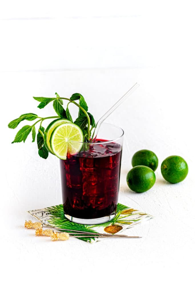 Ice cold glass of agua fresca. This hibiscus iced tea is garnished with mint and lime.