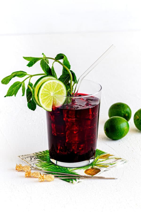 Ice cold glass of hibiscus tea (AKA Agua de Jamaica) garnished with mint, lime and straw.