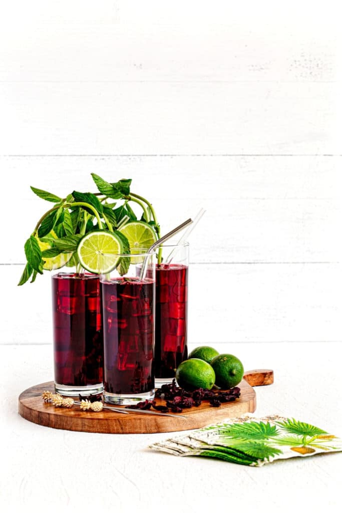 Three tall glasses of Agua de Jamaica Hibiscus Tea. Glasses are garnished with mint and lime.