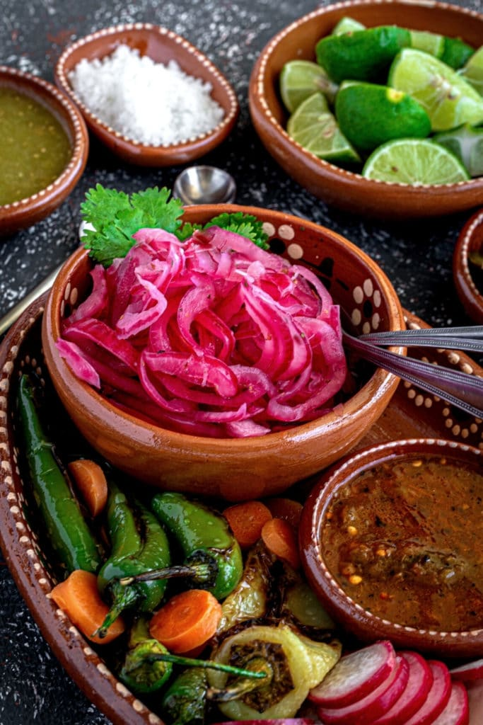 Red pickled onions in a Mexican clay bowl with a metal pickle fork.