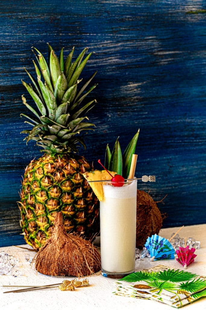 Tropical pina colada served at a beach-front resort. Glass is garnished with a pineapple wedge.