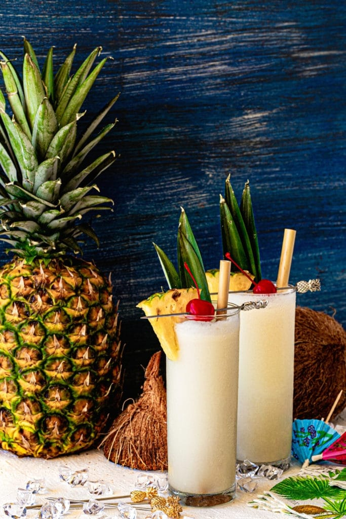 Two homemade pina colada. Glasses are garnished with pineapple, cherries and a bamboo straw.