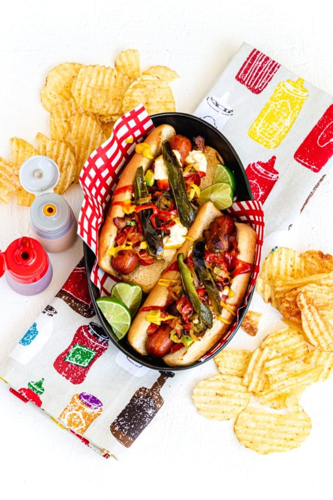 Two Mexican hot dogs in a paper-lined metal serving basket with condiments and potato chips.
