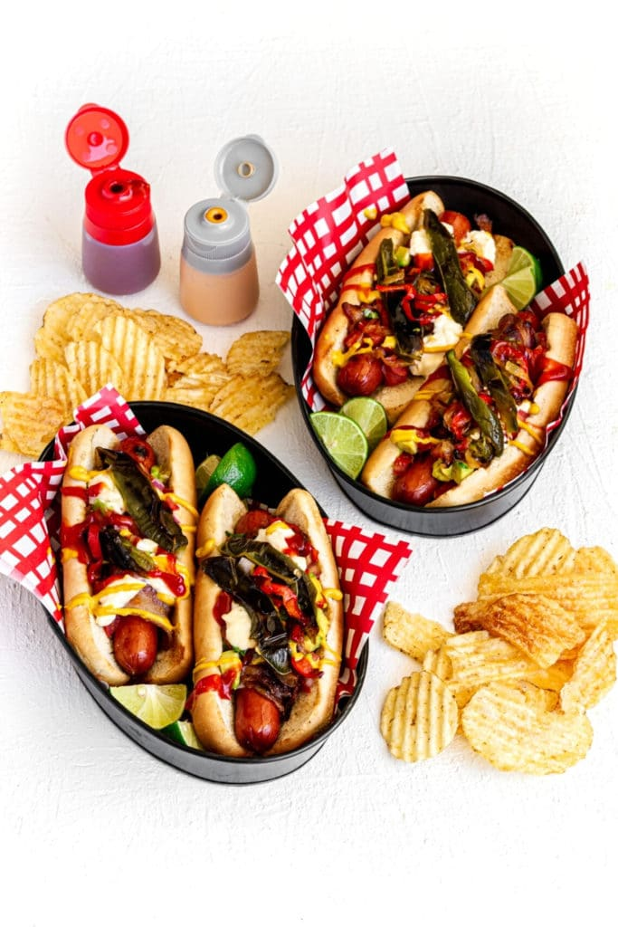 Two metal food baskets with Sonoran Hot Dogs (Mexican Hot Dogs) with condiment bottles and chips.