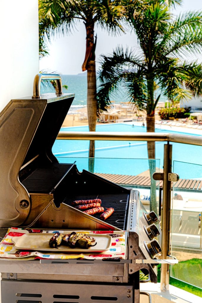 Grilling in Mexico: BBQ with blistered jalapenos and Mexican hot dogs cooking over an open flame.