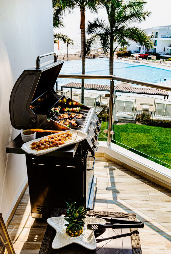 Teriyaki chicken skewers cooking on an outdoor grill.
