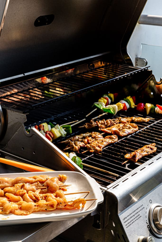 Teriyaki chicken skewers grilling on an outdoor BBQ along with vegetable kabobs.