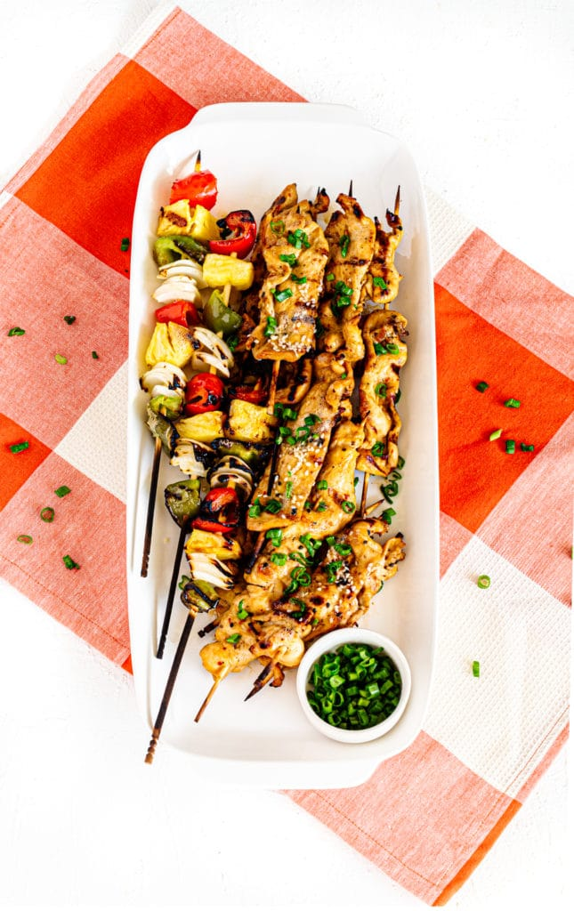 Platter of chicken skewers and veggie kabobs fresh off the grill.