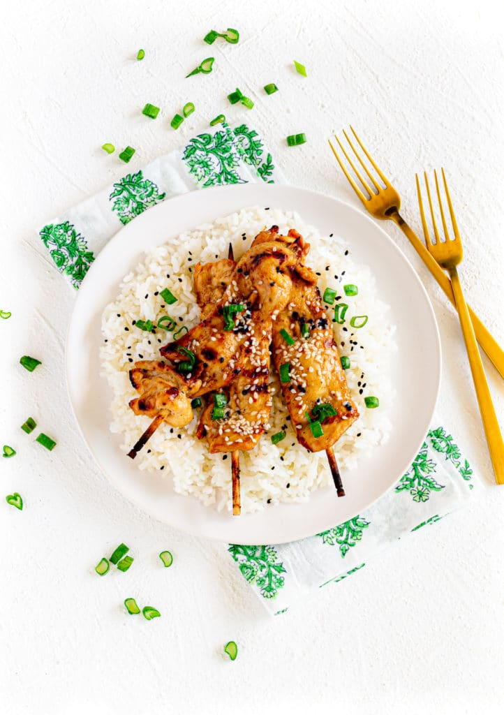 Teriyaki chicken on a stick over fluffy white rice sprinkled with sesame seeds and green onions.