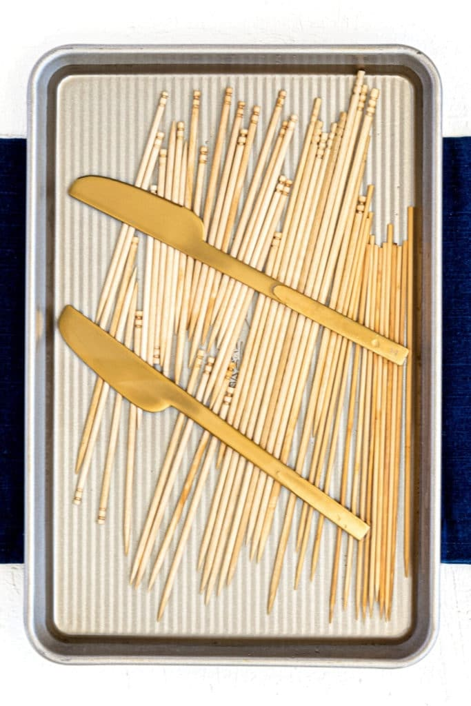 Wooden skewers soaking in water in a baking tray held down with 2 gold knives.