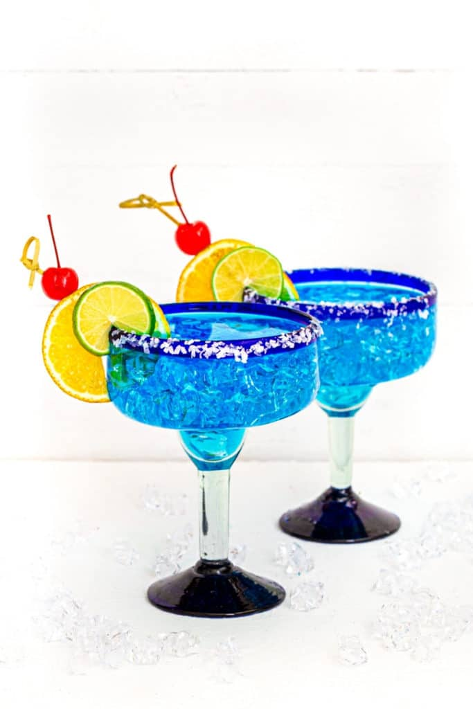 Two Blue Curacao Margarita in Mexican cocktail glasses rimmed with Margarita salt and garnished with fruit.