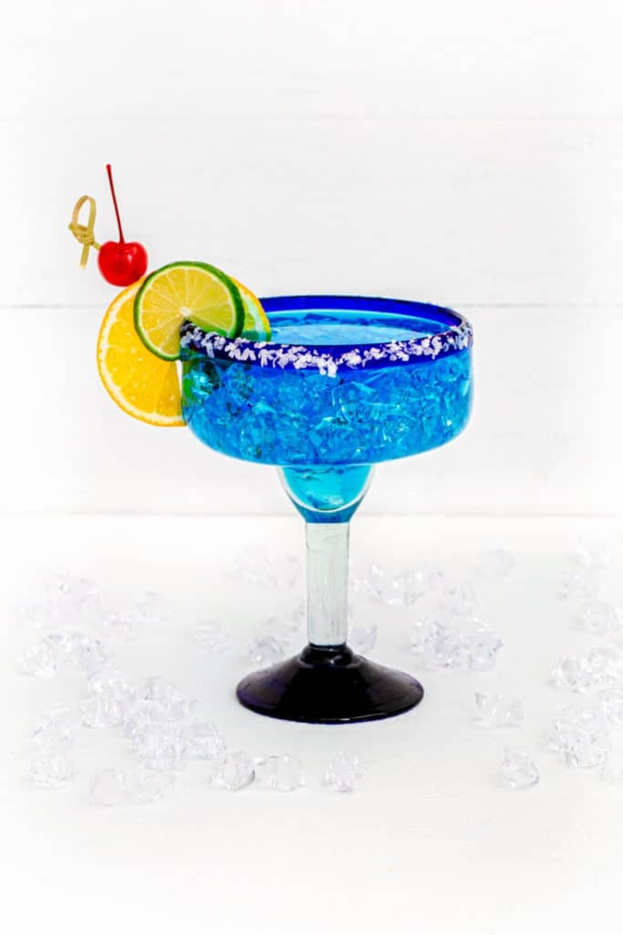 Blue Margarita in a Mexican bar glass garnished with orange slice, lime slice, and Maraschino cherry.