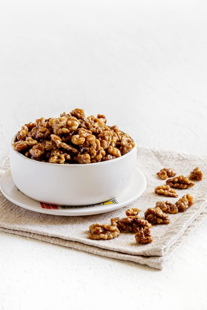 A white bowl filled with candied walnuts for snacking.