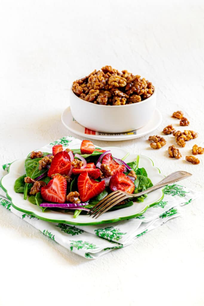 A plated serving of fresh garden salad topped with candied walnuts.