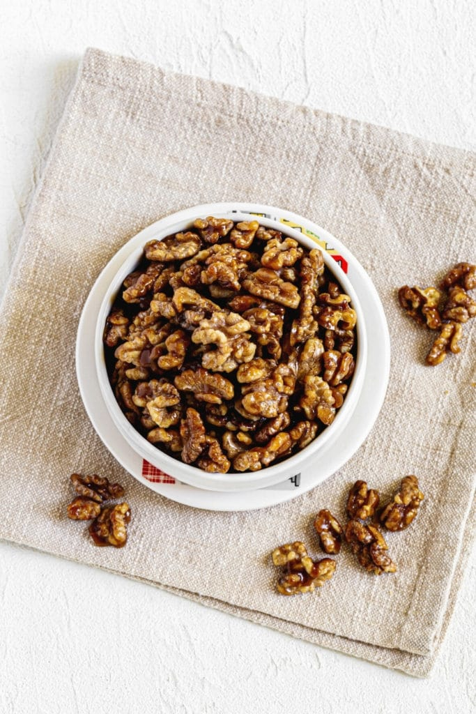 White clay dish of candied walnuts with beige cloth napkin on a white serving table.