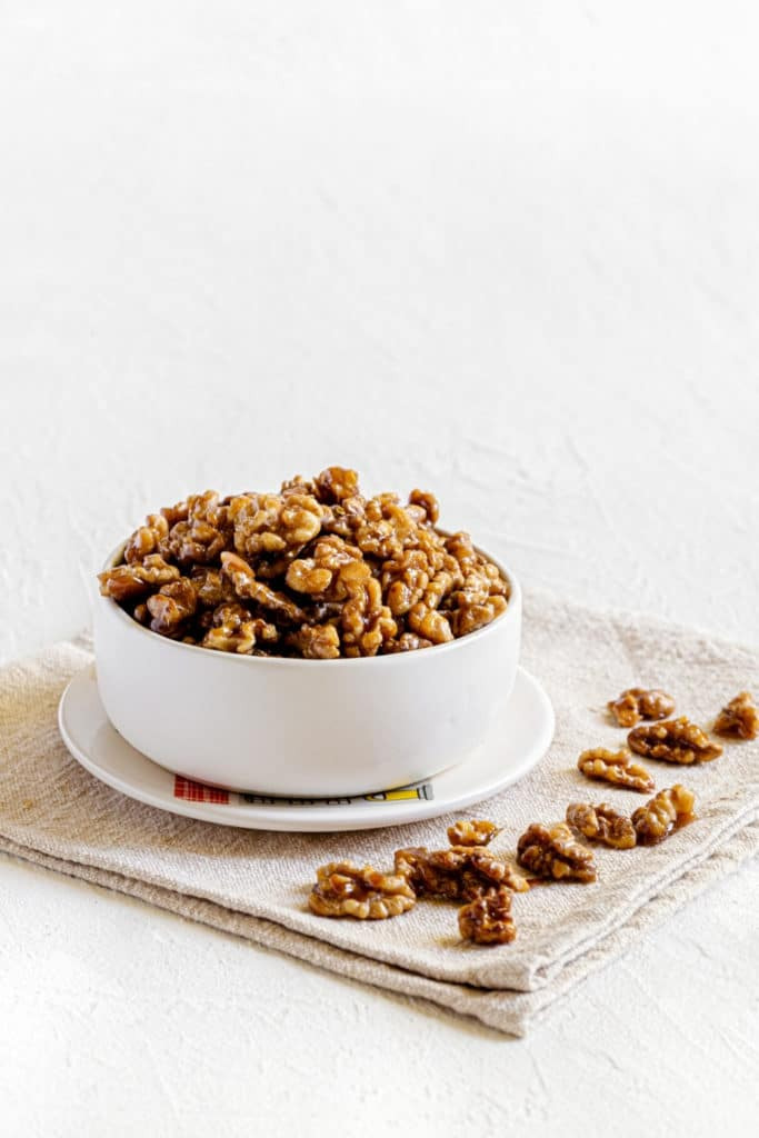 Glazed walnuts overflowing in a small white bowl atop a small plate for snacking.
