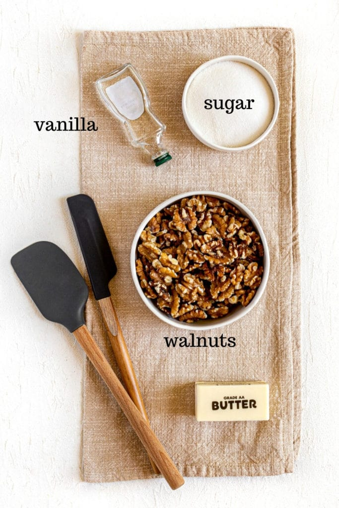 Ingredients for candied walnuts (AKA glazed walnuts): walnut pieces, granulated sugar, butter and vanilla extract.
