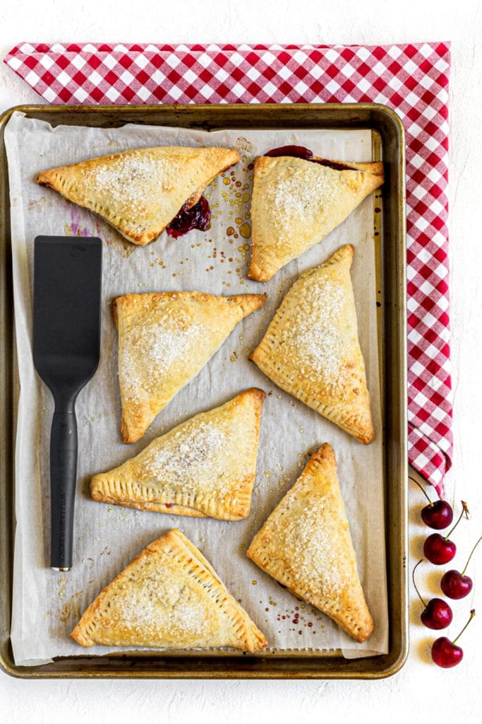 Seven cherry hand pies on a parchment-lined baking tray with a small spatula.