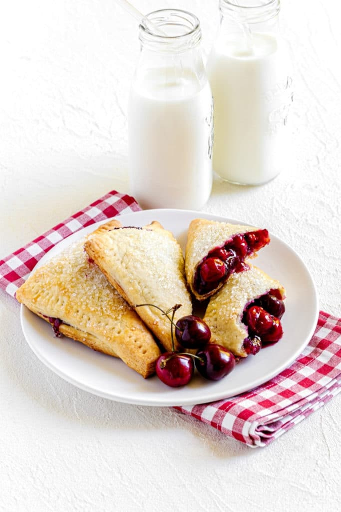 Three homemade cherry turnovers on a white plate with 2 glass containers of milk with straws.