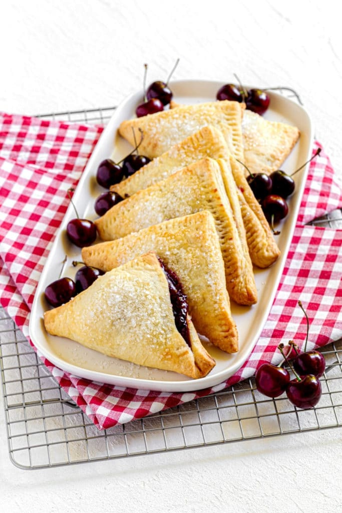 Six homemade cherry hand pies on a white platter next to a scattering of fresh cherries.
