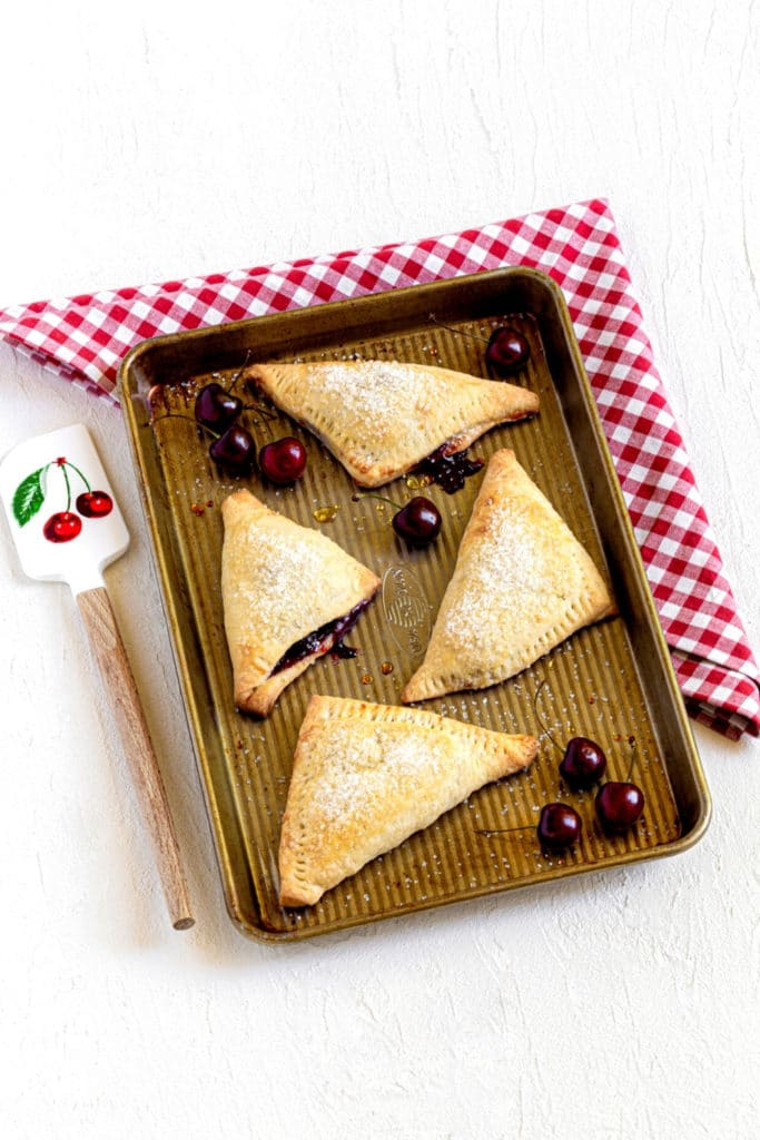 Four cherry turnovers on a small baking tray cooling atop a red/white gingham kitchen cloth.
