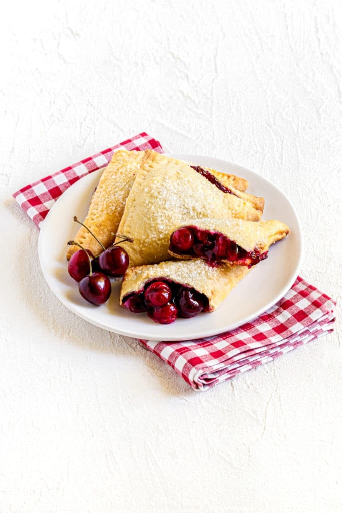 Dessert plate with 3 cherry turnovers. One is torn in half with fruit filling oozing out.