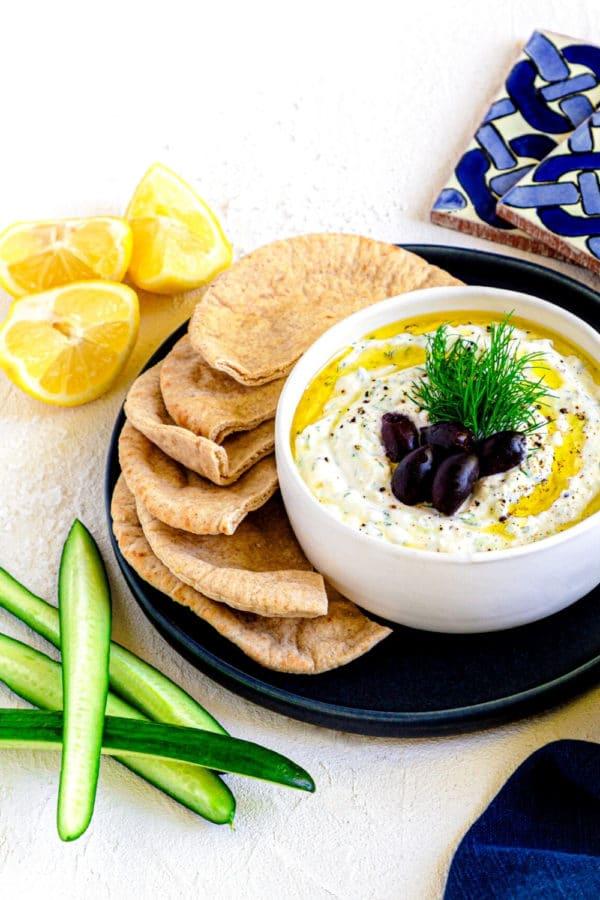Greek gyro sauce in a white bowl alongside fresh pieces of pita bread.