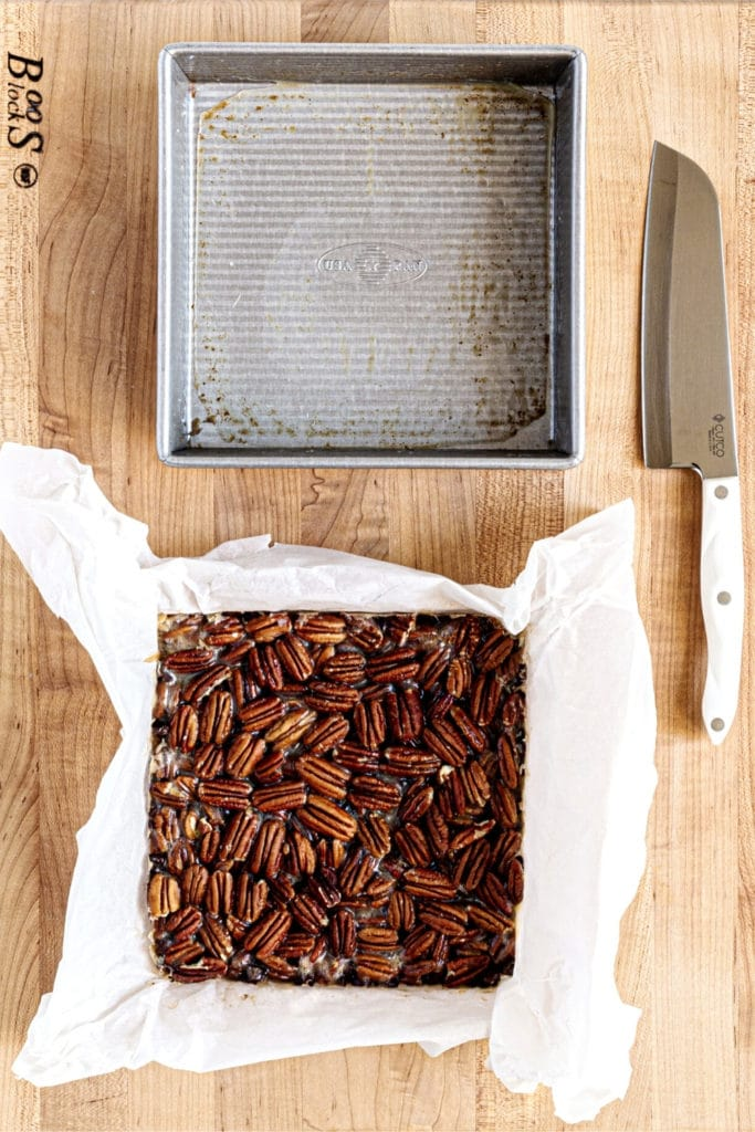 Slab of chocolate pecan bars on wooden board with knife for slicing into Thanksgiving dessert bars.