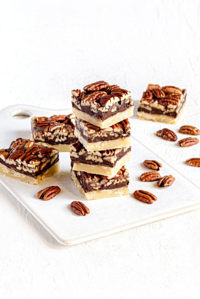 Stack of chocolate Pecan Pie Bars on a white ceramic serving board.
