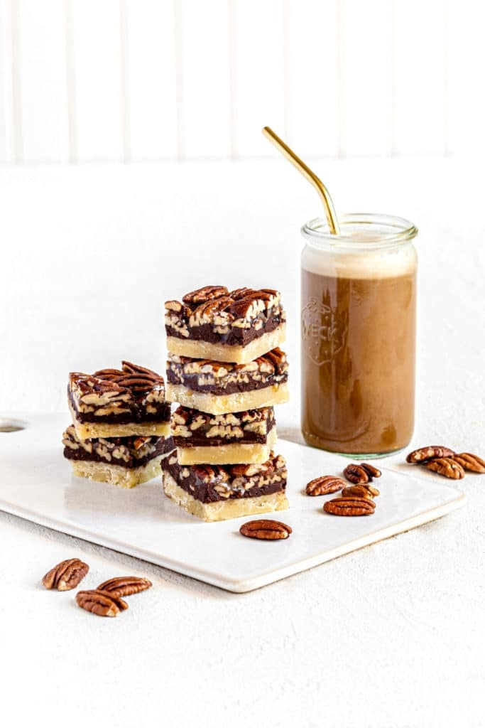 Chocolate pecan bars on white ceramic board next to glass of iced coffee with gold straw.