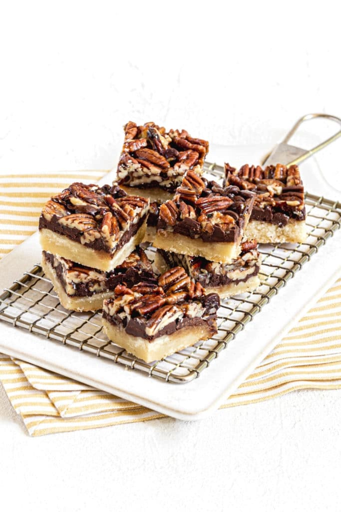 Eight chocolate pecan pie bars stacked on a small metal rack.