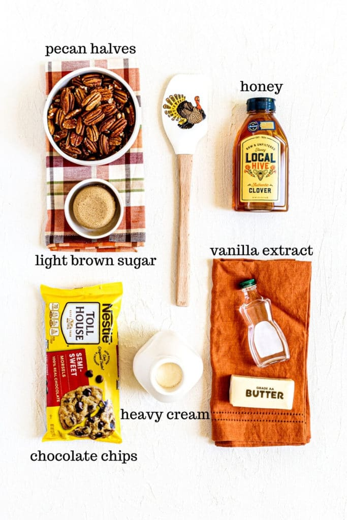 Ingredients for chocolate pecan pie bars filling: nuts, brown sugar, honey, chocolate chips, vanilla, cream, butter.