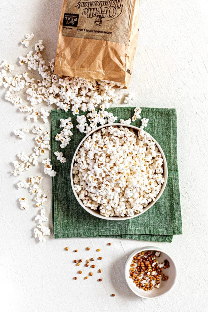 Popped popcorn spilling out onto white tabletop and bowl, with unpopped kernels separated out.